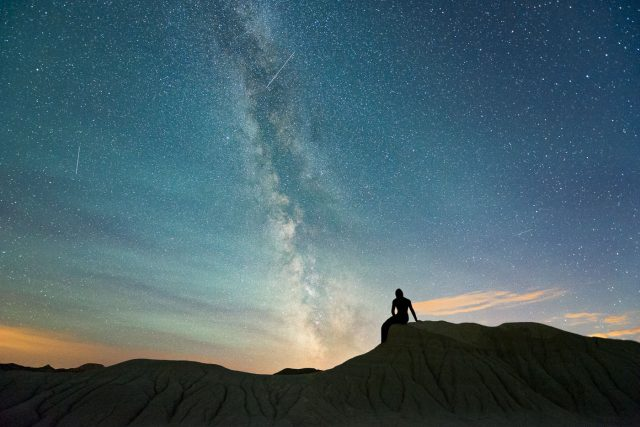 Milky Way and silhouette of woman in dress sitting on sandstone ridge in Dinosaur Provincial Park