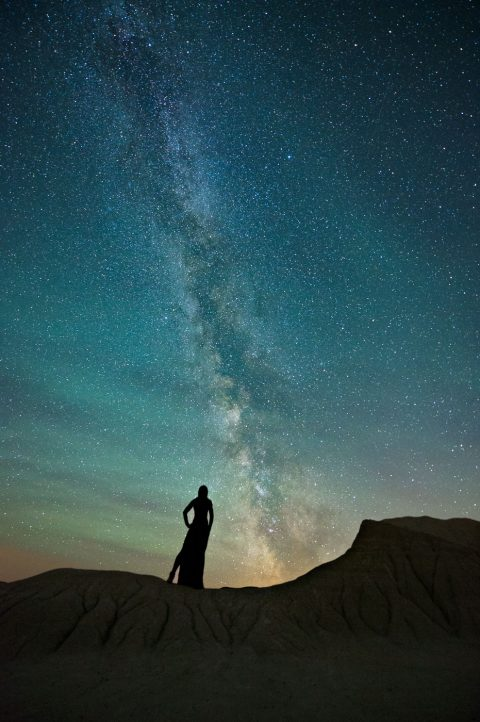 Milky Way and silhouette of woman in dress standing on standstone ridge in Dinosaur Provincial Park