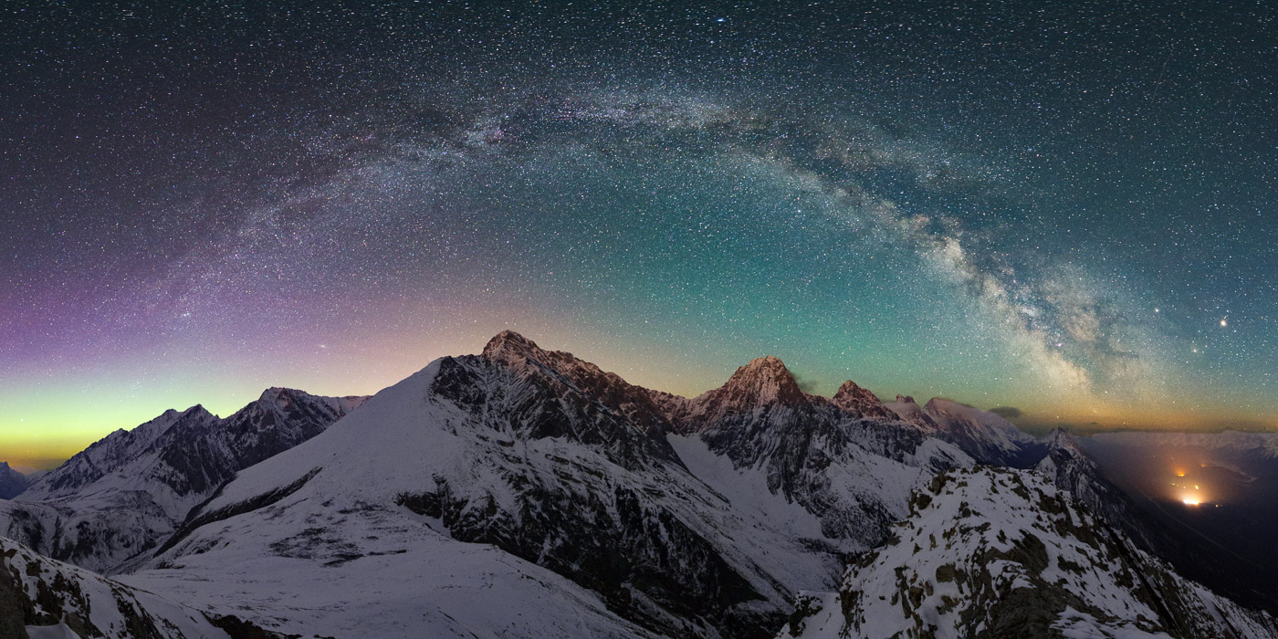 Milky Way arc over snow capped peaks with aurora band in the North, Kananaskis Alberta
