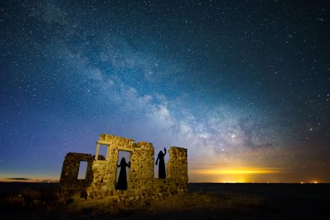 Two cloaked silhouettes in stone building remains with Milky Way, Alberta
