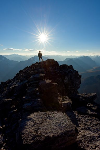 Silhouette of hiker on a summit ridge with a sunburst above