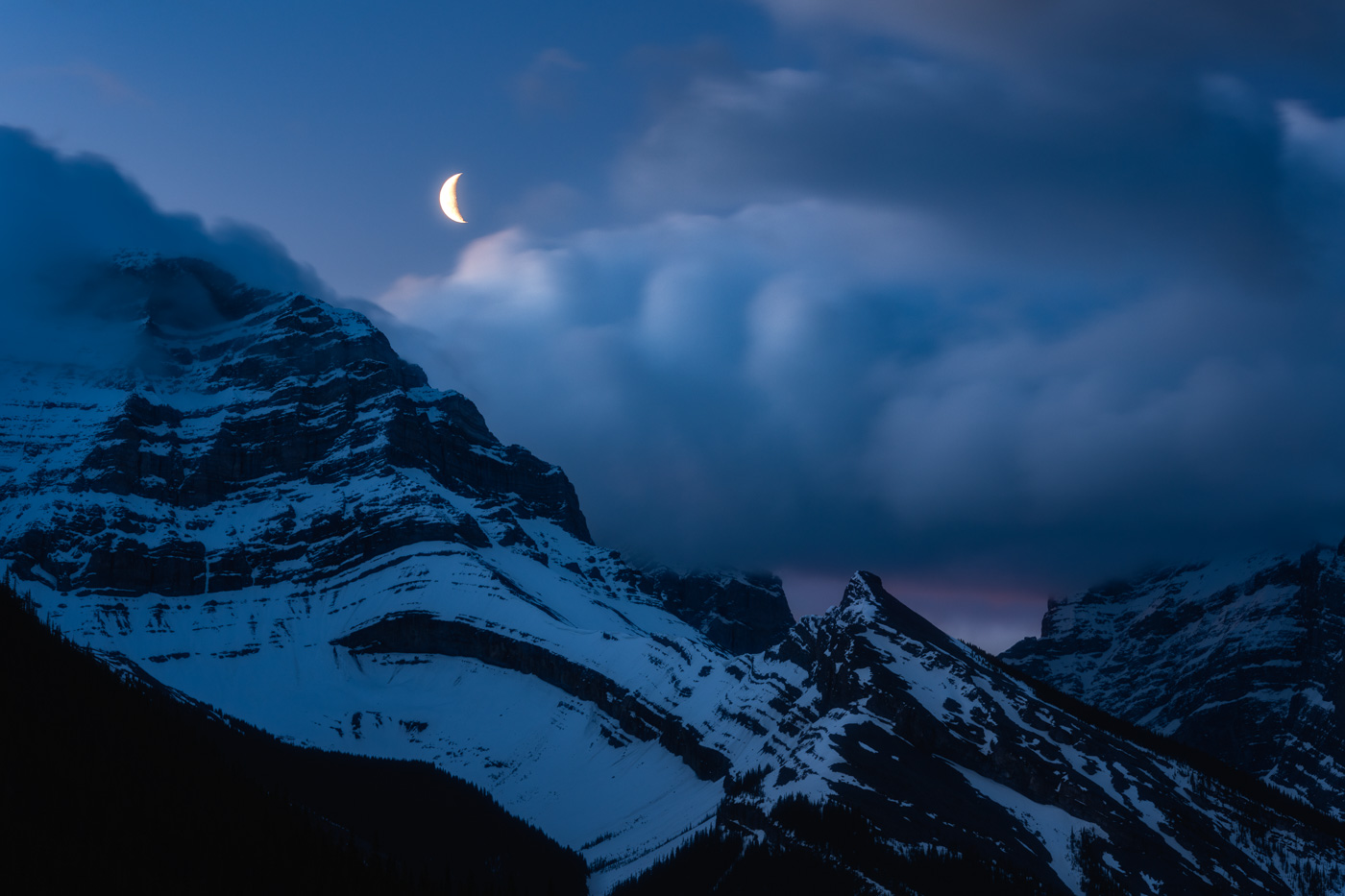Moon over puffy clouds and Mount Lougheed at Blue Hour