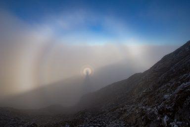 Silhouette of hiker in broken spectra over inversion in highwood pass