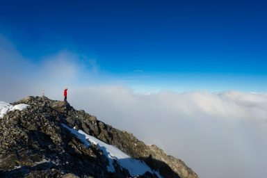 Hiker in red jacket and yellow helmet looks over inversion from the summit of Mount Rae