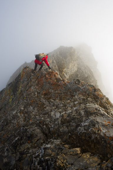 A male in red jacket scrambles over a rock band covered in verglass on Mount Rea