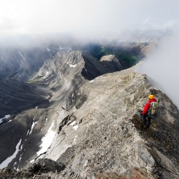 Hiker stop on narrow ridge to take in exposed view with low clouds obscuring mountain tops