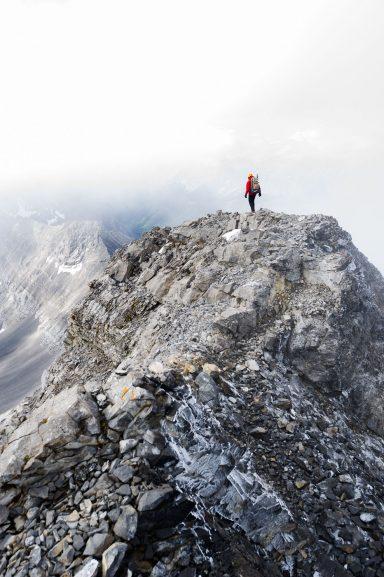 Hiker walks along a ridge covered in verglass in HIghwood Pass