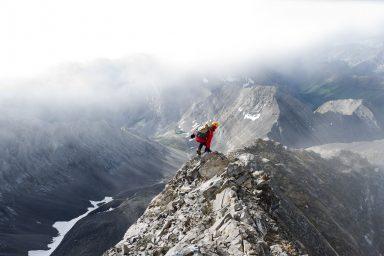 Male scrambling in red jacket and orange helmet along narrow ridge in the Canadian Rockies