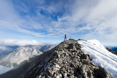 Woman stands on summit of Mount Rea, Highwood Pass