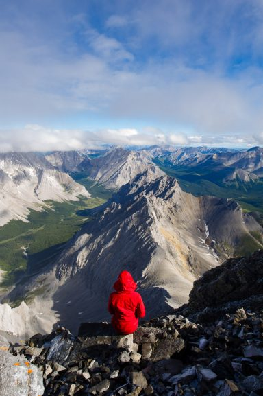 Hiker in red hooded jacket surveys view of mountains and valleys