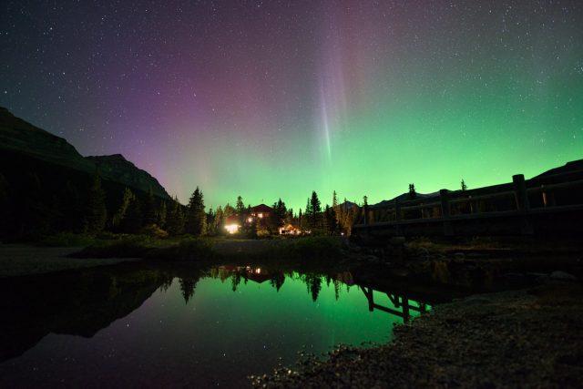 Aurora Borealis and Num Ti Jah Lodge lights reflecting in Bow Lake