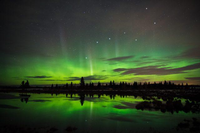 Aurora borealis and big dipper reflect in small pond in Alberta