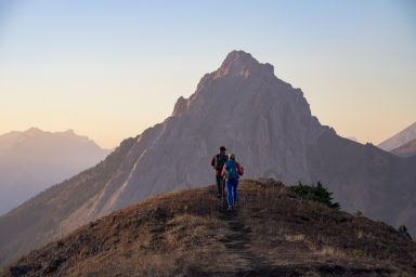 A male and female hiker walk along Pocaterra ridge during sunset