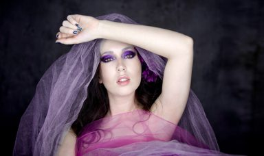 Ring light portrait of dark haired woman with purple and pink Tulle
