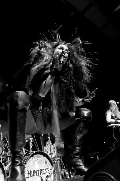 Jill Janus crouching and singing while a fan blows hair crazily, Calgary