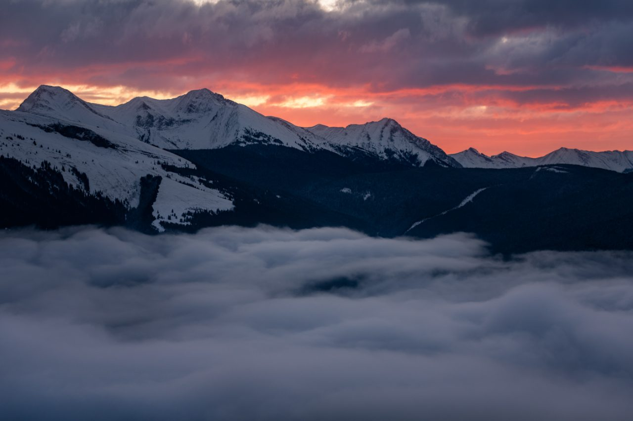 Inversion in the Bow Valley snowy Mountains with red clouds at sunrise