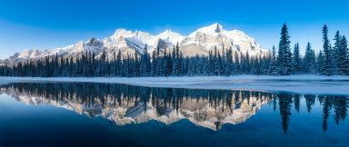 Mount Rundle covered in snow and frosted tree reflecting in the bow river