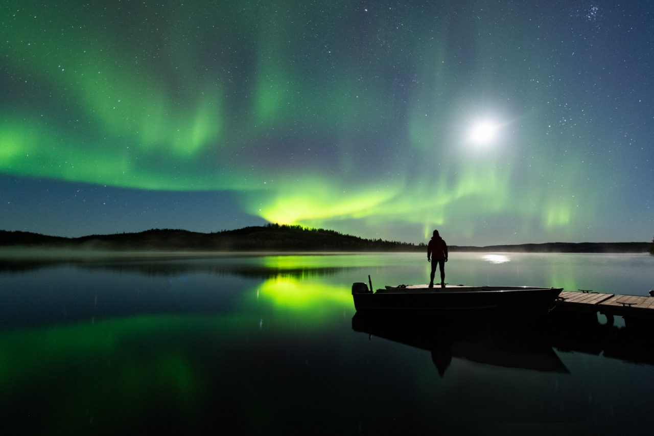 Woman watching Aurora Borealis and Moon reflecting in lake from fishing dock