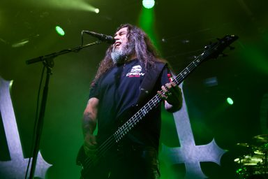 Tom Araya singing and playing bass with inverted crosses on stage, Calgary