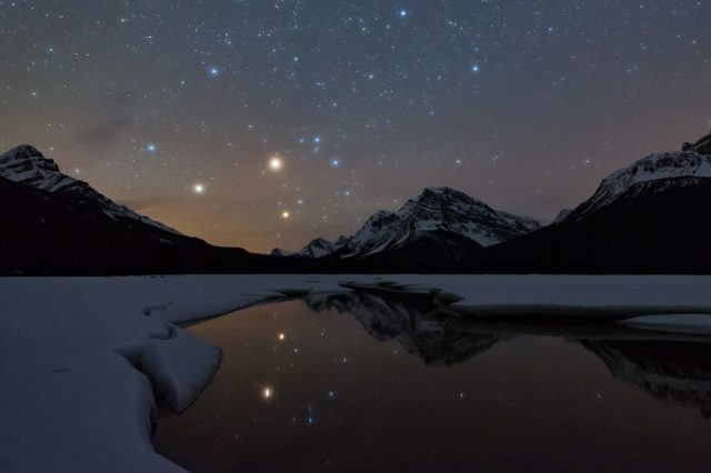 Stars and mountains reflect in small opening of frozen lake, Icefields Parkway
