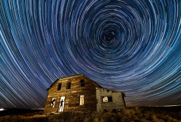 Star Trails over light painted abandoned house with silhouettes in doorways