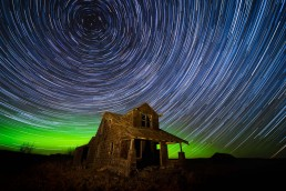Star trails and northern lights over abandoned house in Alberta