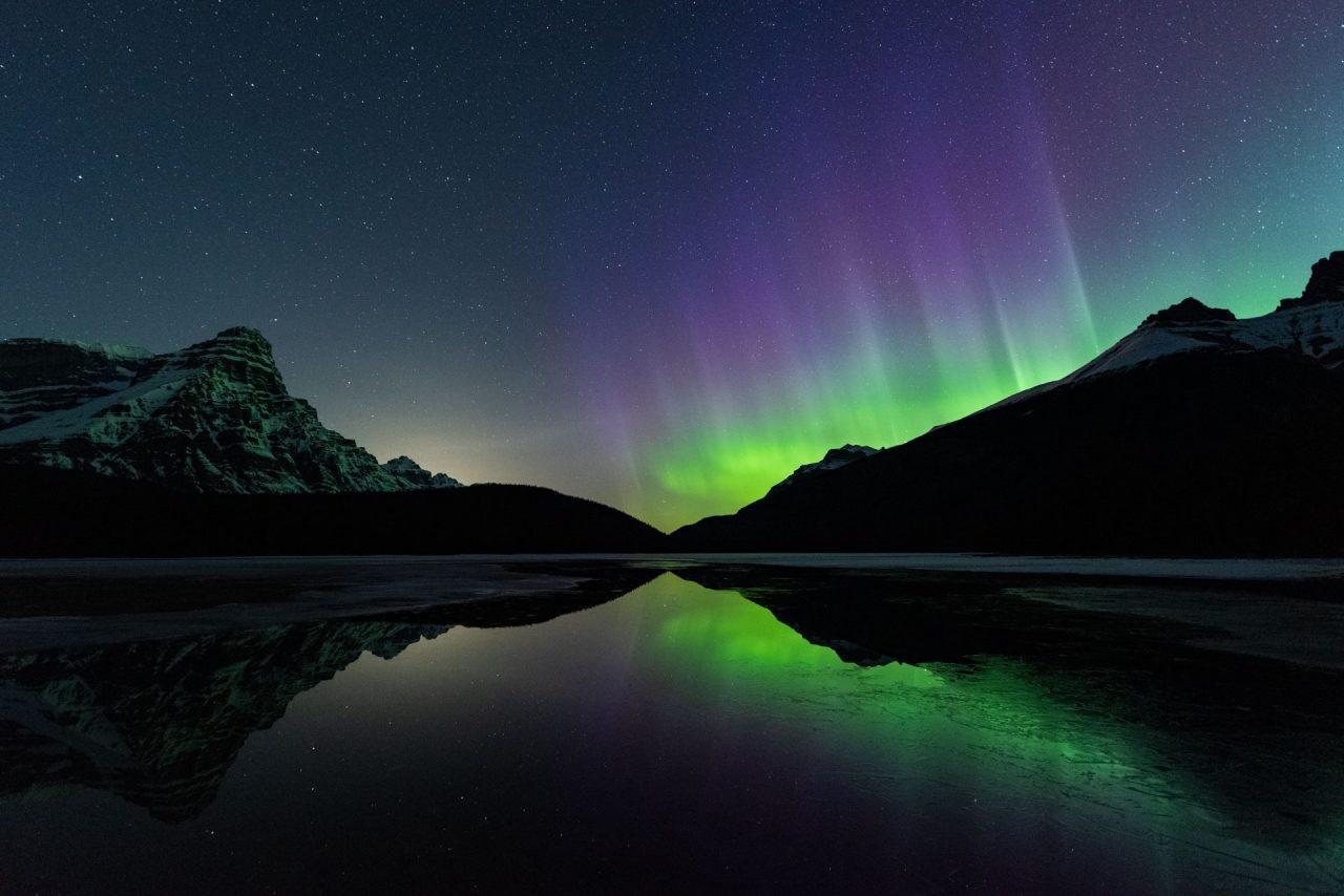 Green aurora with purple pillars dancing behind mountains next to Mount Chephren in Banff