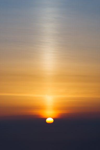 Sun rises above clouds creating vertical beam, Southern Alberta