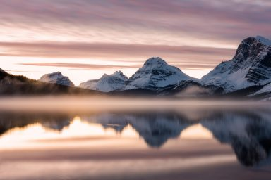 Sunrise colours, mist and mountains reflecting in Bow Lake