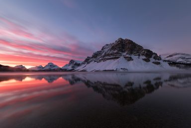 Lines of pink clouds next to Crowfoot Mountain reflecting in Bow Lake