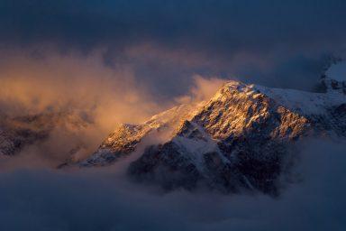 Dramatic sunrise light hitting clouds and mountain summit in Kananaskis