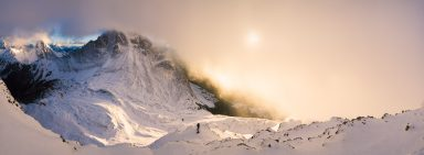 A photography shoots sunrise from a snowy mountain slope as cloud being to lift