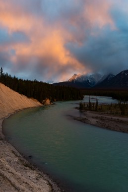A burst of orange clouds over the Athabasca River in Jasper