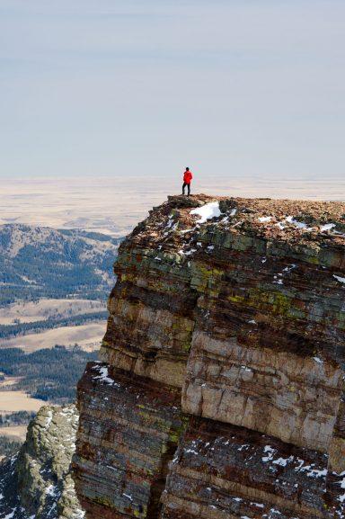 Hiker in red jacket stands on a cliff with multicoloured layers looking at the Souther Alberta Prairies