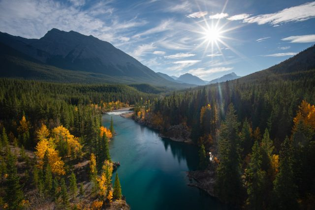Sunburst over Cline river with fall colours lining the banks