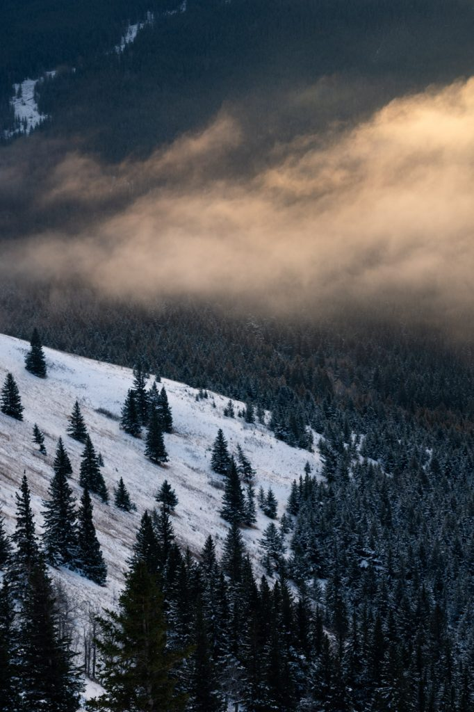 Sun lit clouds drifting over a snowy mountain ridge
