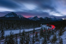 End of Train light blinking through a long exposure during twilight at Morants Curve, Banff National Park