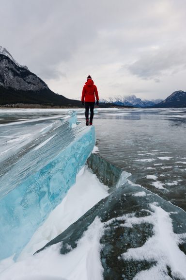 Woman in red jacket walks along cracked blocks of ice on Abraham Lake