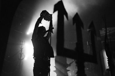 Erik Danielsson holding a skull overhead on stage at Flames Central, Watain