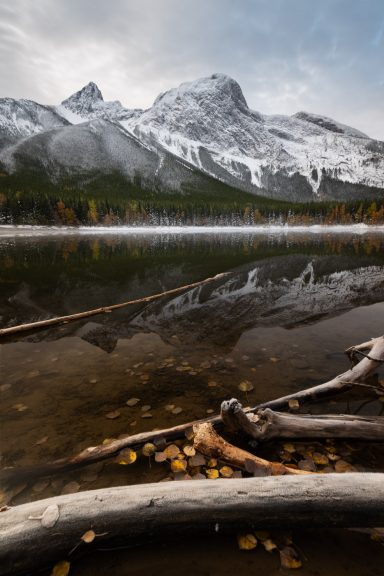 Fall leaves and colours with snow covered Wedge Mountain Reflecting in Wedge Pond