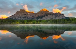Sunrise Aplen glow on the tops of Mount Kidd, fall colours and mist reflect in Wedge Pond