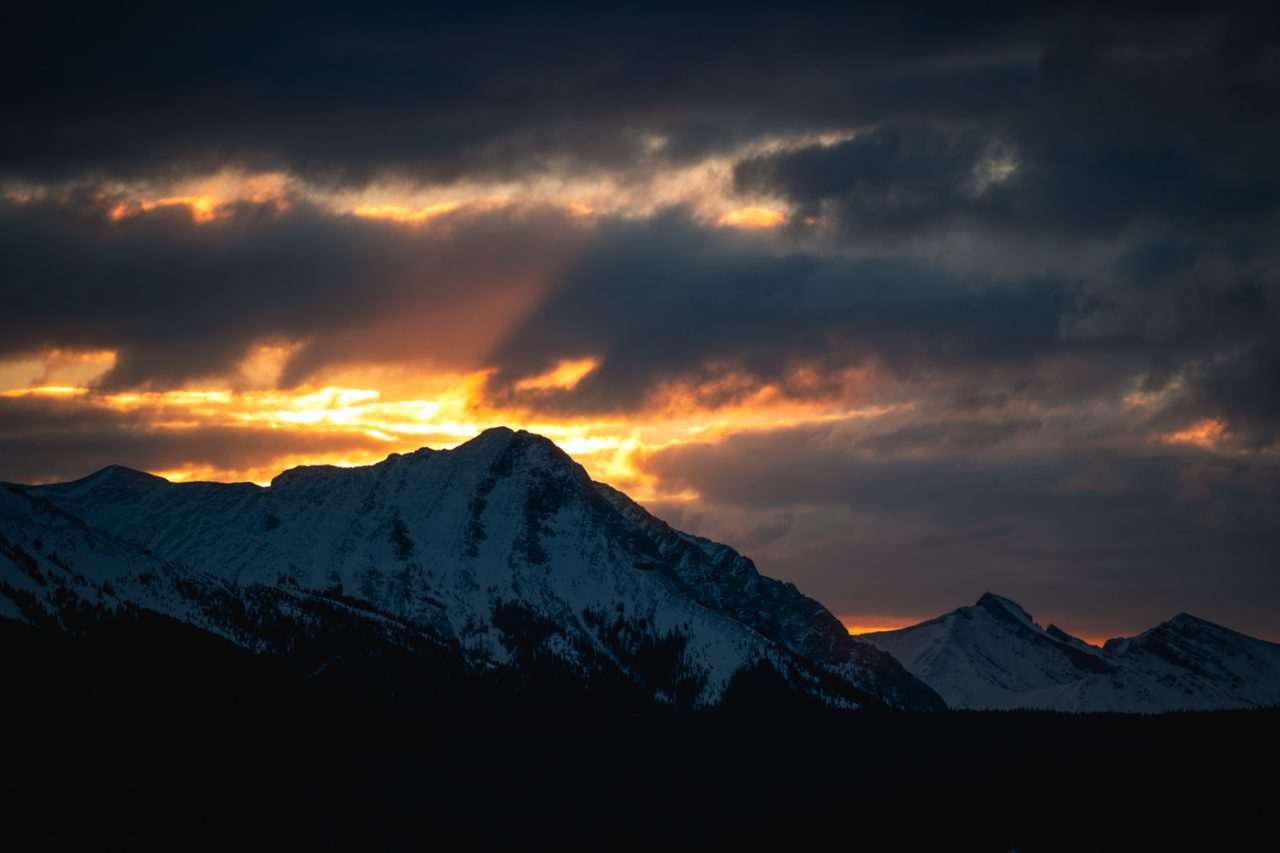 Yellow sunlight framing a snow covered mountain at sunrise in the Bow Valley