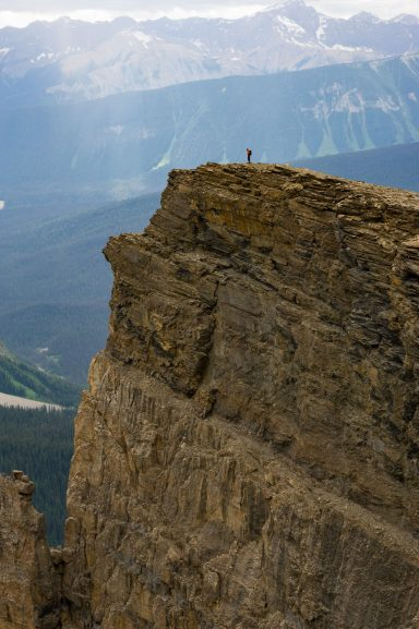 Tiny hiker stands on golden coloured cliff on Wapta Mountain