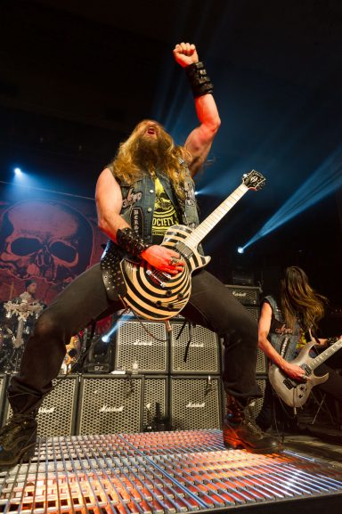 Zakk Wylde playing guitar and throwing a fist in the air