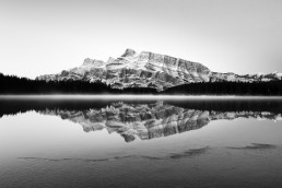 Mount rundle reflecting in two jack lake with a bright mist across the lake and icy edge, monochrome