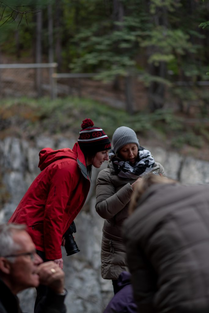 Monika Deviat looking at a participants camera during a photography workshop in Jasper