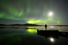 Silhouette of person standing on a dock with fishing boat, aurora borealis and moon reflecting in water
