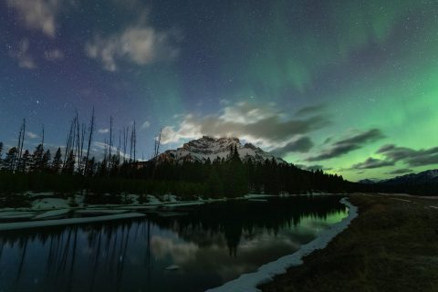 Aurora and moonlit clouds over snowy Cascade Mountain in Banff