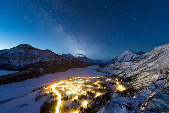 Milky Way fading in blue hour over the snowy town of Waterton