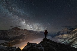 Hiker standing on a ridge over Waterton Lakes and Town with Milky Way over Vimy Peak